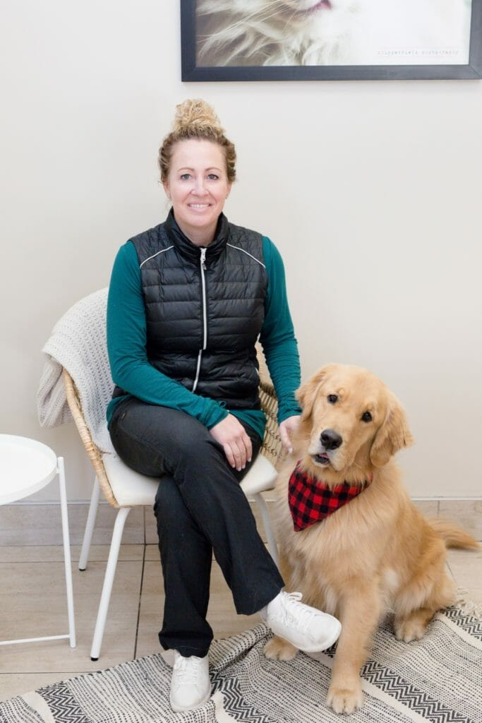 Managing partner of a veterinary clinic sitting with a golden retriever